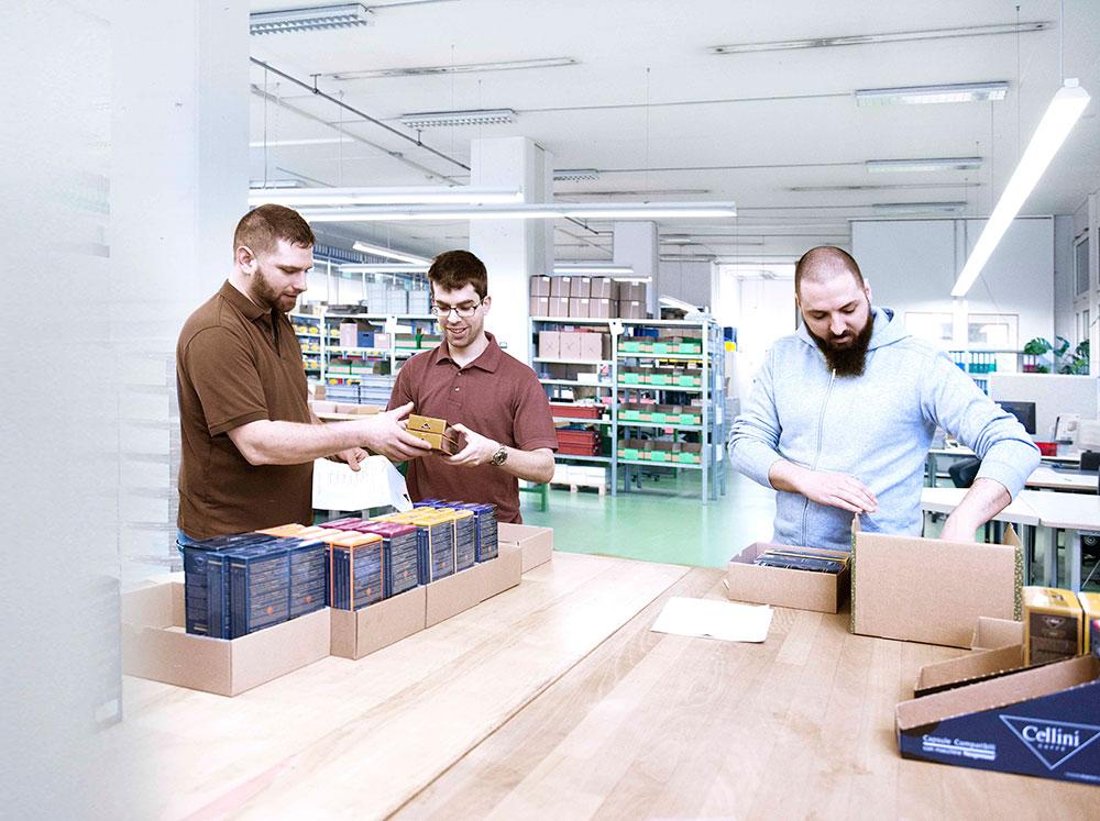 Im Lager stehen 3 Mitarbeiter an einem Packtisch und kommissionieren unterschiedliche Produkte.